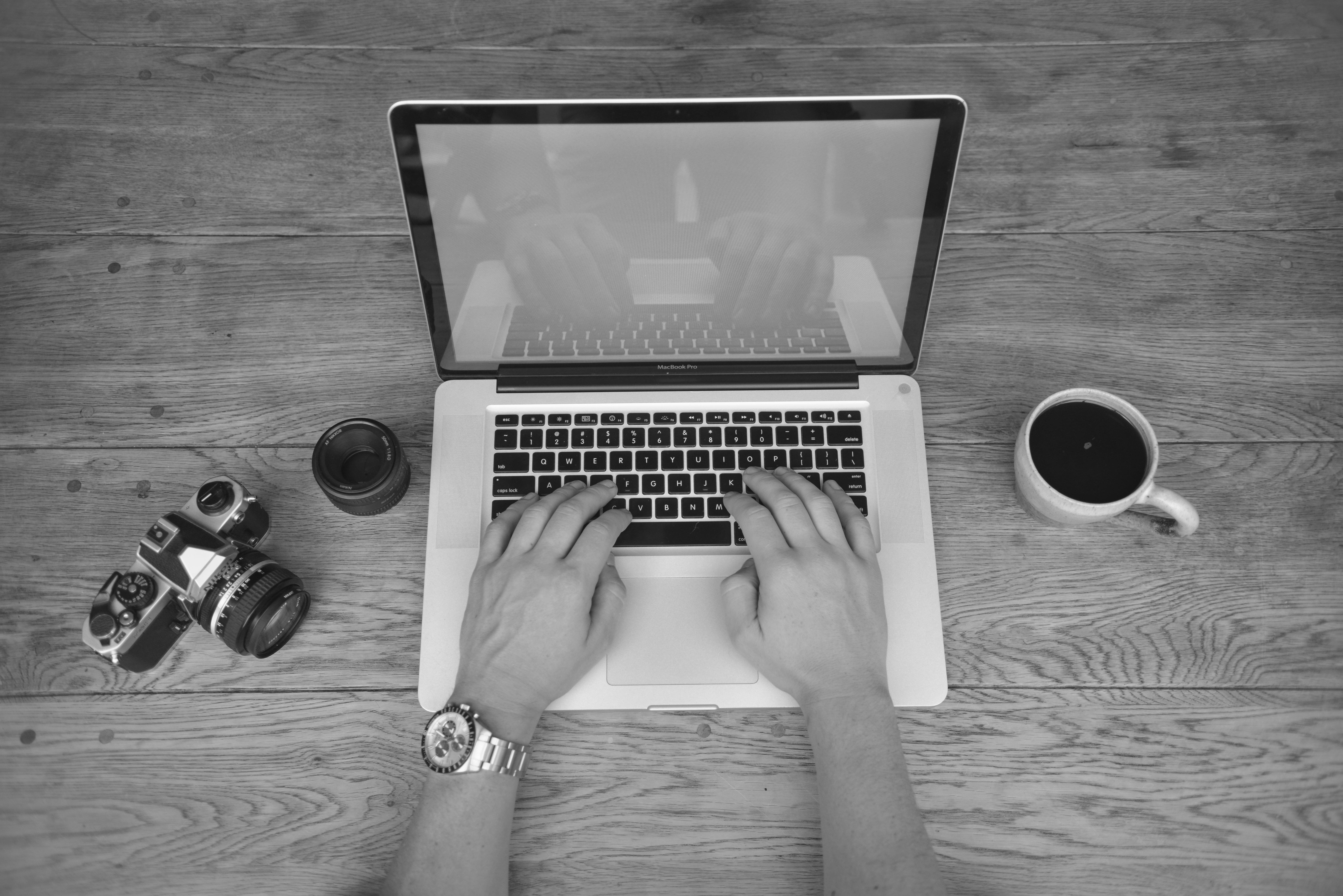 Manos escribiendo en portátil con al lado un café, una cámara de fotos y un objetivo