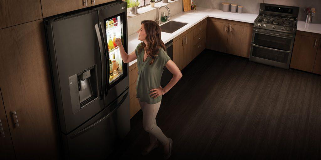 Chica activando la pantalla transparente del frigorífico inteligente LG