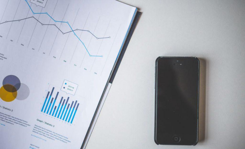 las empresas y el iot representado por un móvil y unas gráficas de datos