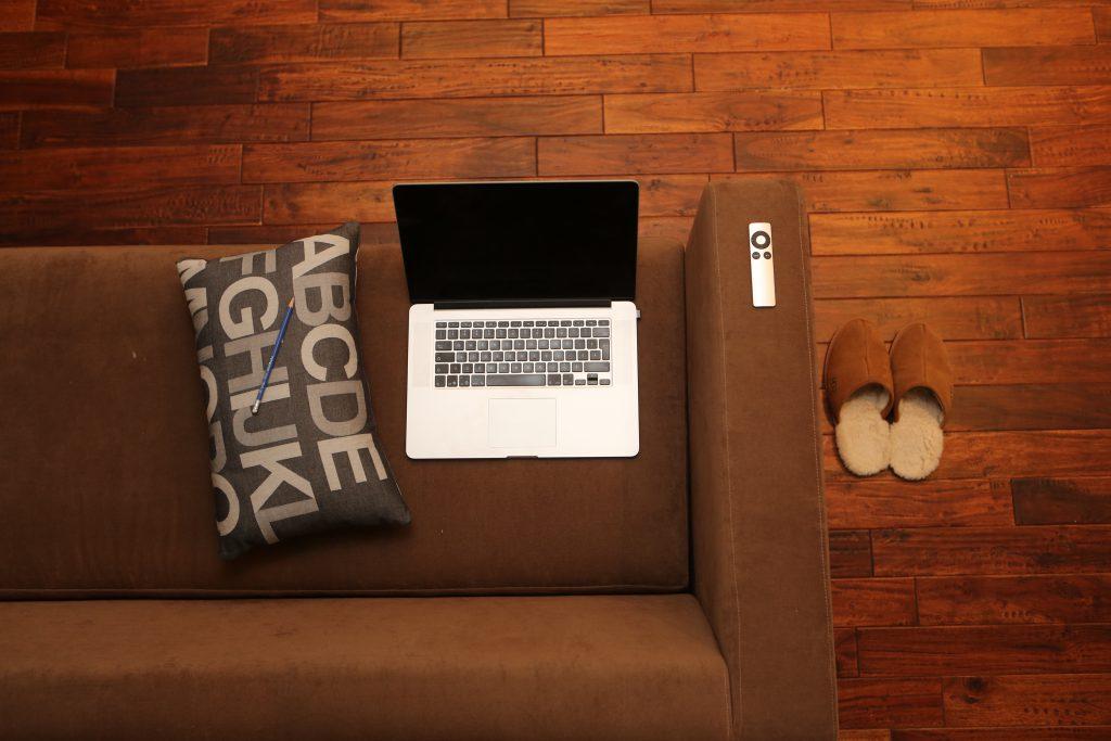 Sofá con cojín, portátil, mando a distancia y zapatillas
