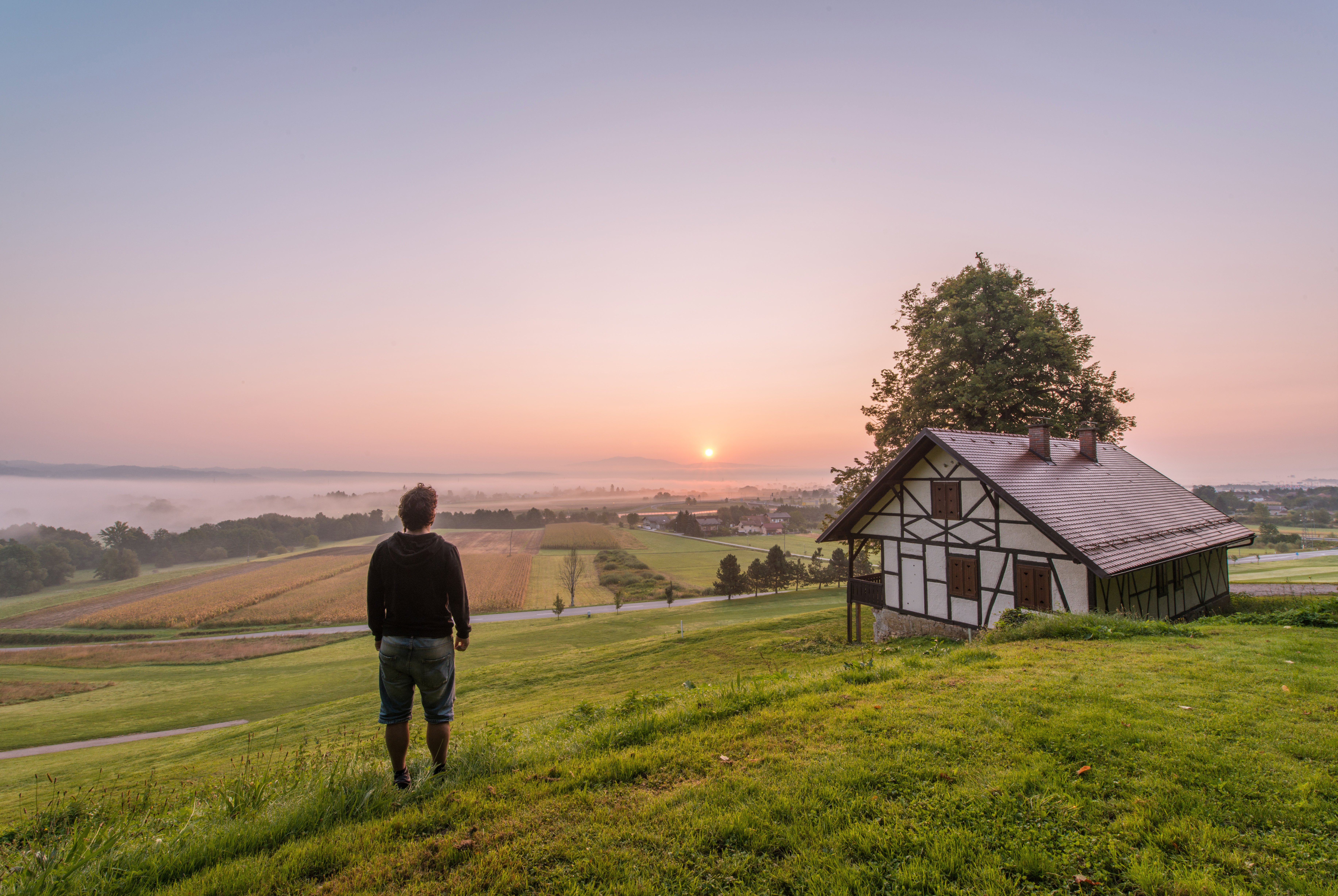 Man posing in front of beautiful sunrise by the medieval house in rural countryside of Slovenia