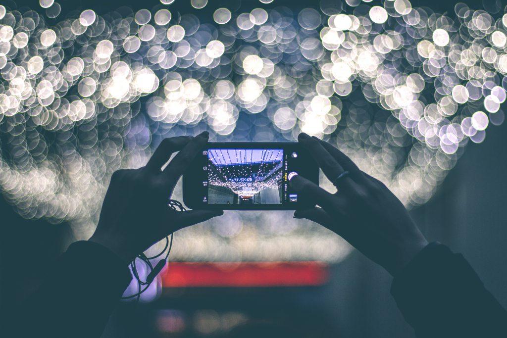 Persona haciendo un foto a unas luces con su smartphone
